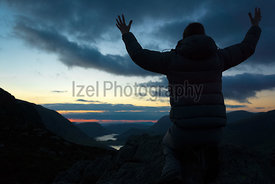 A man worshiping God from the summit of a mountain.