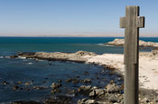 granite cross, a replica of the one erected by Bartholomeu Diaz, the first European explorer to enter the bay at Diaz Point, ...