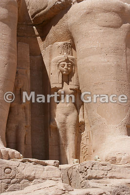 Statue of Muttuy, mother of Ramesses II by the leg of the damaged colossus, facade of the Sun Temple of Abu Simbel, Egypt
