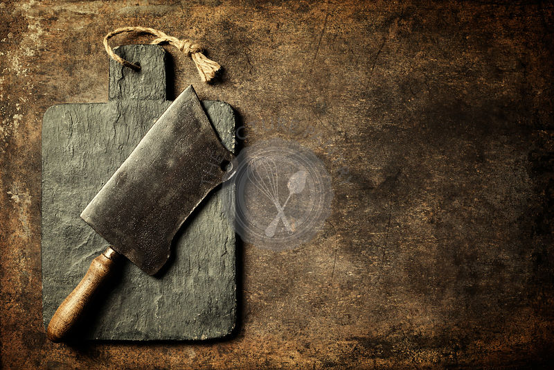 Vintage cutting board and meat cleaver with space for text on old metal background, close-up