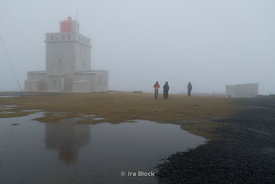 People walking by the Dyrholaey Lighthouse on the Southern Coast of Iceland on a foggy day.