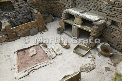 Interior of House 1, Skara Brae neolithic farming village, showing (clockwise) central hearth, box bed, dresser and grinding ...