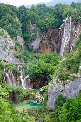 Overview of tourists on boardwalk and bridges, dwarfed by the Great waterfall (Veliki Slap) above and Sastavci waterfall belo...
