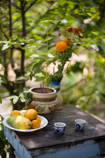 Vietnam - Tay Ninh. Fruit and incense are offered at a shrine on a family farm