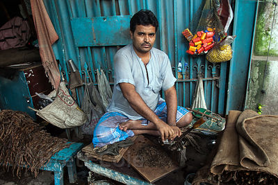 A man cuts tobacco on Strand Rd. in Kolkata, India.