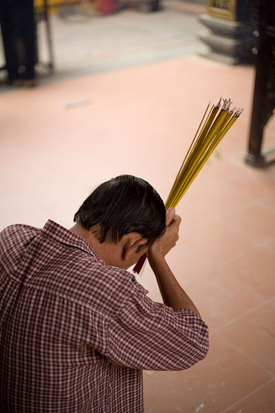 A man prays with incense at the Hoi Quan On Pagoda