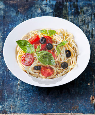 Pasta with tomato and basil on blue wooden background