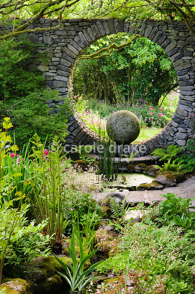 A stream, fringed with astilbes and ferns, runs down hill to the circular pool that reflects the Moon window in a stone wall,...