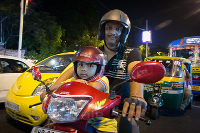 Father and son ride a scoot in heavy traffic near South City Mall, Jodhpur Park, Kolkata, India. Thankfully they'e both weari...