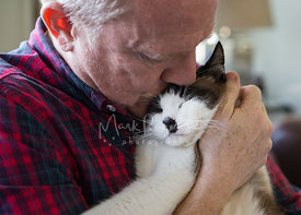 Close-up of Man Holding and Kissing a Cat on the Head