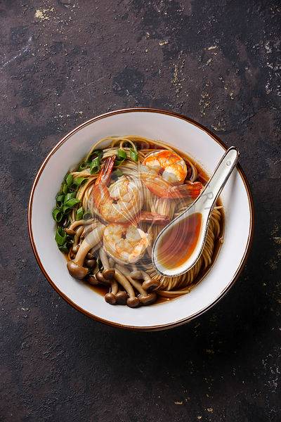 Asian Ramen noodles with prawns and shimidzhi mushrooms on dark background copy space