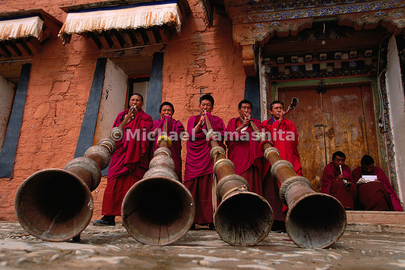 Labrang Monastery, novice monks (trapa), practice blowing the dungchen, traditional 13-foot horns, that will be used in Buddh...
