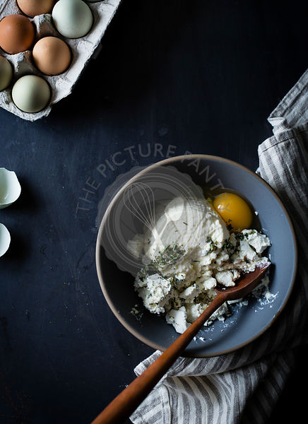 Ricotta soft cheese in a mixing bowl with eggs and herbs.