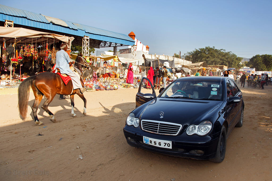 A horse passes a sleek black late model Mercedes in the desert at the Pushkar Camel Fair, Pushkar, Rajasthan, India
