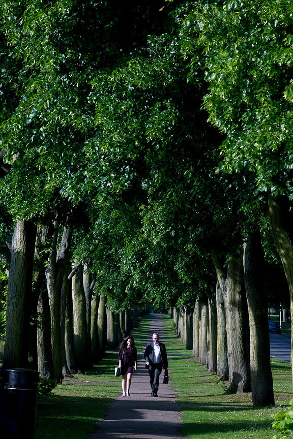 UK - Letchworth Garden City - A couple in suits on their way to work walk down the Braodway, a long tree-lined avenue