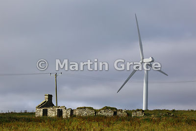 Ruined croft house at Evie, West Mainland, Orkney, with wind turbine behind