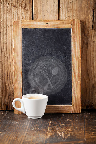 Coffee cup and Vintage slate chalk board on wooden background