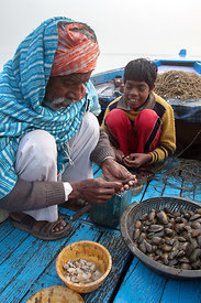Fisherman and his grandson shucking clams (?) on the Ganges River, Varanasi, India.
