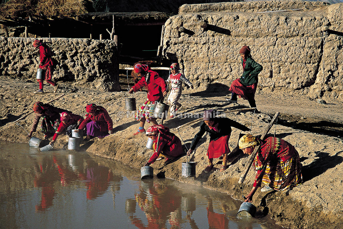 Tajik girls from Akmquit, China collect water from a pool in an oasis.