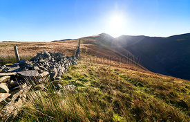 A stone wall leading up the mountain ridge towards Ladyside Pike and Hopegill Head on a sunny day in the English Lake Distric...