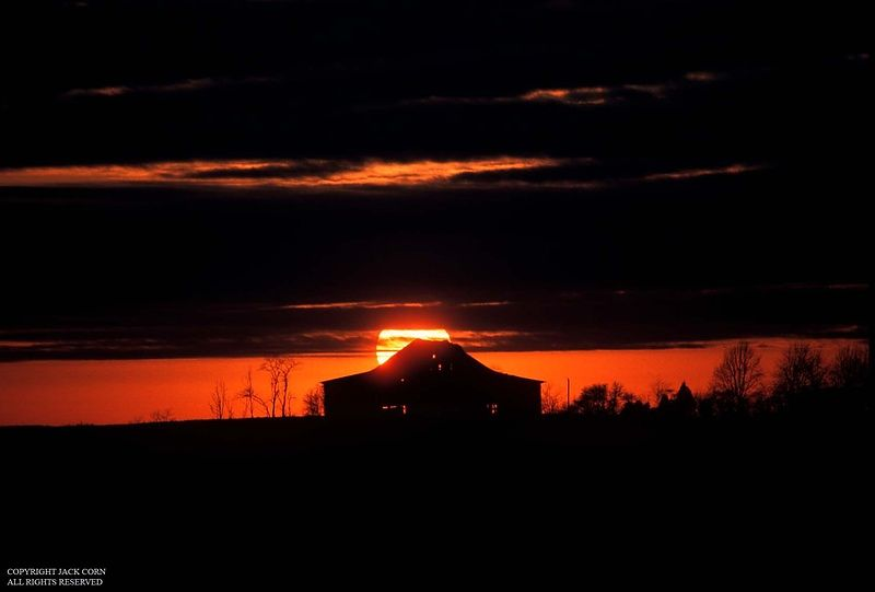 Red sun behind Kentucky barn