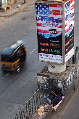 "People sleep beneath a billboard for the show ""America's Got Talent"" in Bandra East, Mumbai, India."