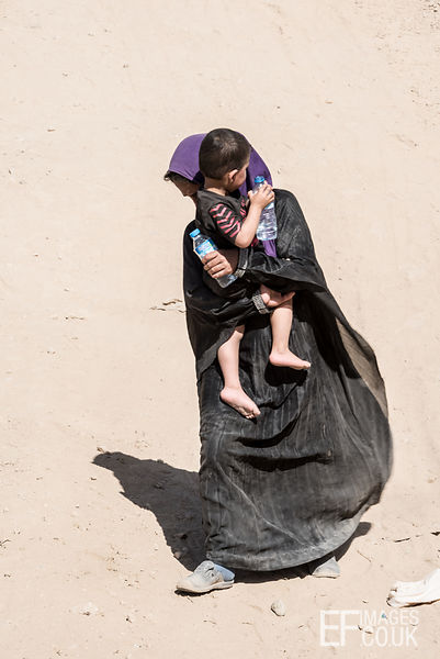 A woman carries only water and her son as she escapes on foot from the battle for Mosul. Mushaarifa, Mosul, Iraq, 7th May 2017