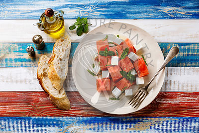 Watermelon salad with feta cheese and mint on wooden background