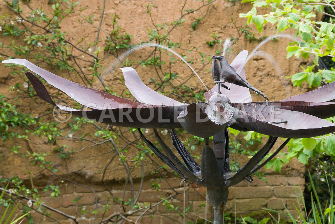 Metal fountain by Michael Chaikin inside the Pond Garden, designed and built with cob by Mathew Robinson. Planting includes H...