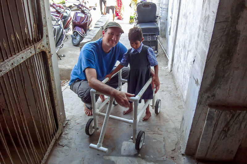 Helping Miss Pooja learn to walk with a walker we built