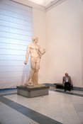 A tourist sits by a statue in the National Archaeological Museum in Naples
