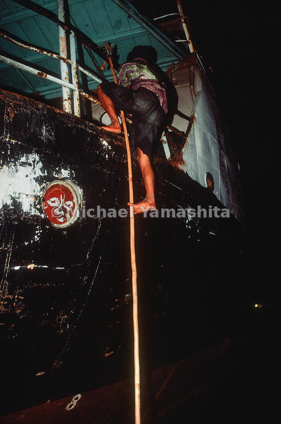 Pirates board ships under cover of night using poles with hooks and speed boats. .Indonesia