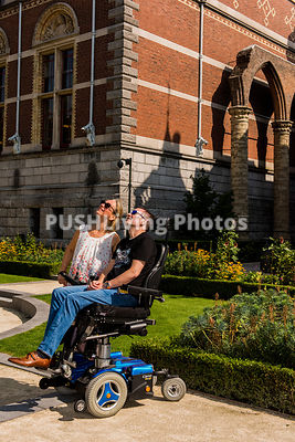 Couple using power wheelchairs talking in a museum garden