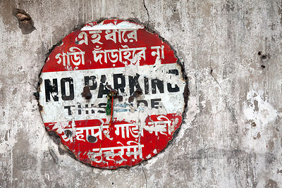 Weathered No Parking sign on a cement wall at Newmarket, Kolkata, India.