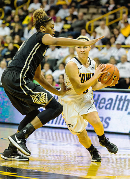Purdue's Torrie Thornton (4) defends Iowa's Whitney Jennings (15) during the first half of play at Carver-Hawkeye Arena in Io...