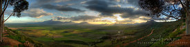 Panoramic view of sunbeams shining through clouds at sunset over lush, bright, green farm fields, dirt road leading to farm b...