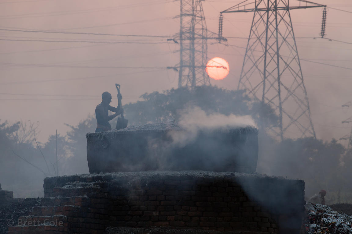 A man stirs a leather incinerator against a backdrop of electrical towers and the setting sun, near the town of Bantala, in t...