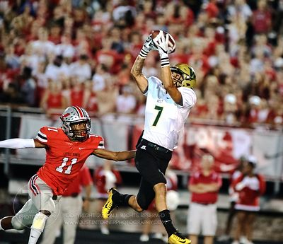 Iowa City West's Traevis Buchanan (7) catches a pass over Iowa City High's Marquel Poole (11) during the first half of play a...