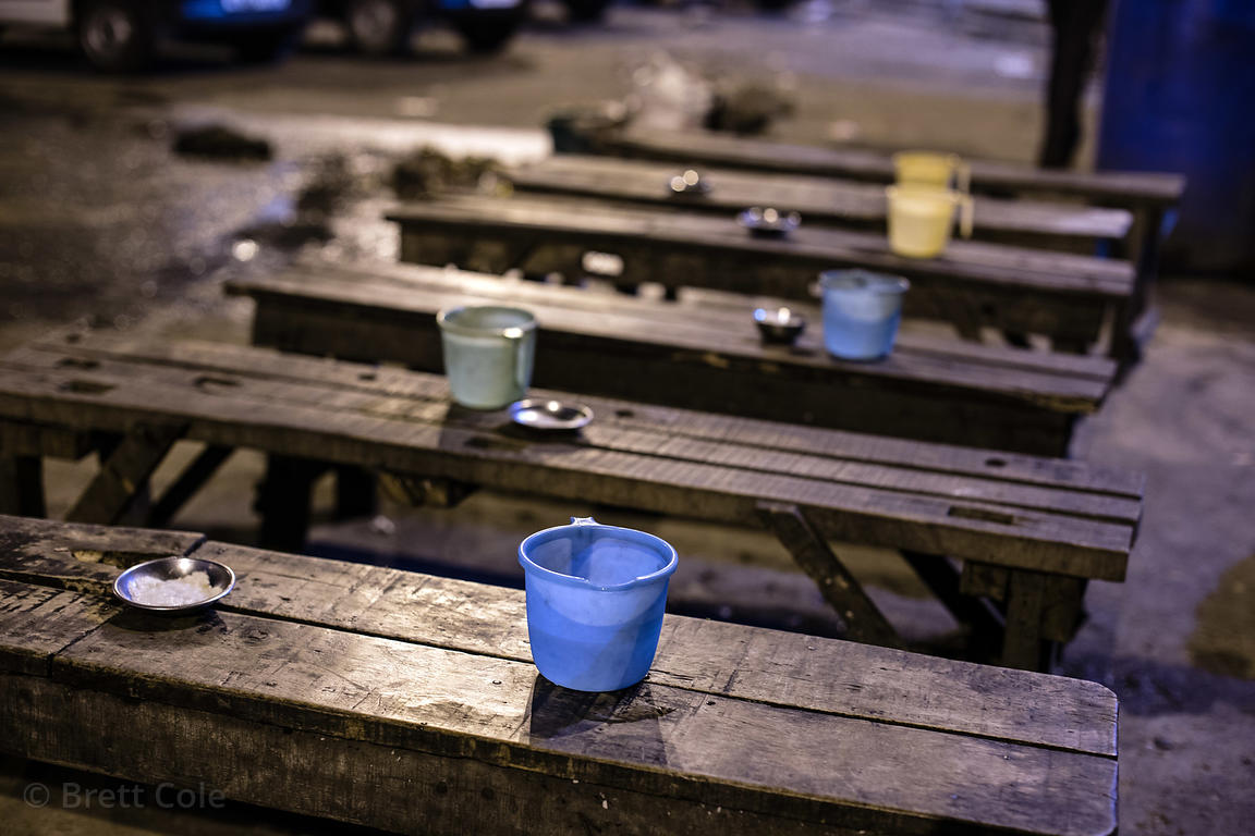 Water cups on wooden benches at night, Babughat, Kolkata, India