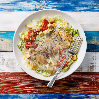 Caesar salad with chicken breast and fork on wooden background