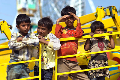 A group of boys hope for a passerby to pay their way at a carnival ride, Pushkar, Rajasthan, India