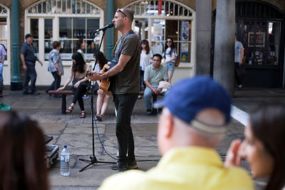 UK - London - A musician sings and plays guitar to an audience in the Covent Garden Market Piazza.