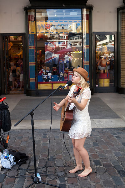 UK - London - A female busker sings and plays guitar to a crowd in Covent Garden Market,