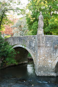 Bridge over the River Frome, 1400, with 18th century statue of Britannia installed by Peto. Iford Manor, Bradford-on-Avon, Wi...