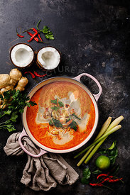 Tom Yam kung Spicy Thai seafood soup with shrimp, coconut milk and lemon grass in casserole copy space