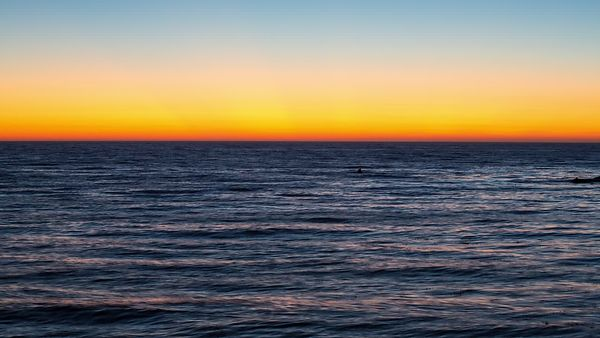 Wide Shot: Dark Pacific Waters Below A Golden Ring Of Venus