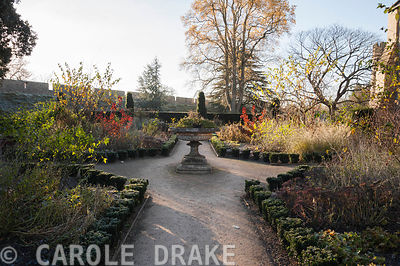 The formal East Garden at the Bishop's Palace garden in Wells, with decorative urn and beds edged with evergreen euonymus pla...