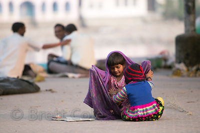 Two sisters play along the Ganges River in Haridwar, India
