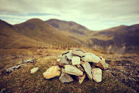 A cairn, pile of stones marking a mountain top, waypoint in the English Lake District. Summit of Outerside with Sail and Crag...