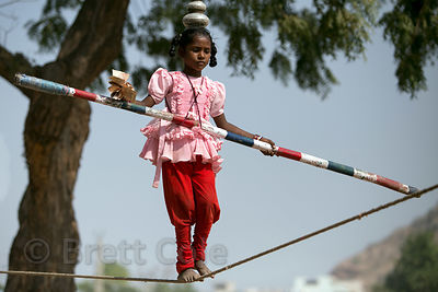 A girl does a slack wire routine at a carnival, Pushkar, Rajasthan, India
